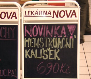 """Ilustrace: Reklamní cedule s nápisem: """"Novinka: Menstruační kalíšek za 690 Kč""""."""